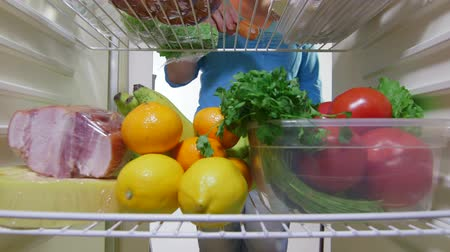 lodówka : Housewife takes out vegetables from the fridge