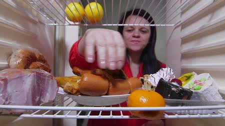 hűtőgép : Hungry woman eating fat food inside fridge at night