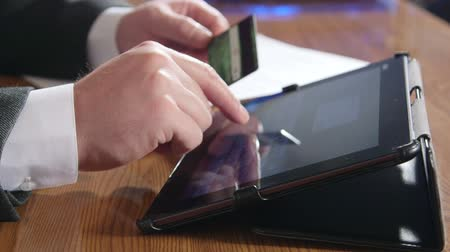payment : Businessman using credit card and digital tablet computer for online payment Stock Footage