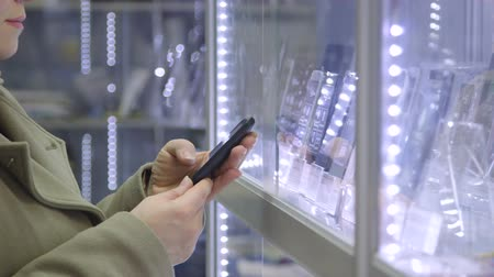 elektronický : Customer chooses smartphone in electronics store