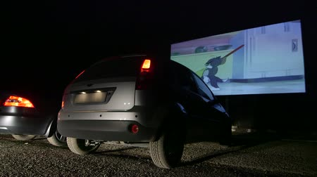řídit : SIMFEROPOL, UKRAINE - JANUARY 03, 2014: Drive-in movie theater showing Tom and Jerry cartoon at night, in the foreground parked cars