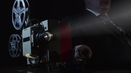 filmes : Man dressed in suit watching 16 mm film on old flickering movie projector Stock Footage