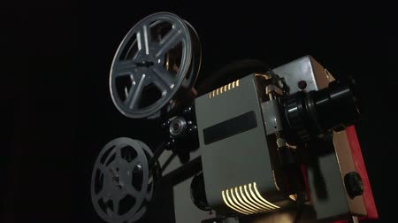 葡萄收获期 : Dolly: Vintage 16 mm movie projector projecting film in a dark room