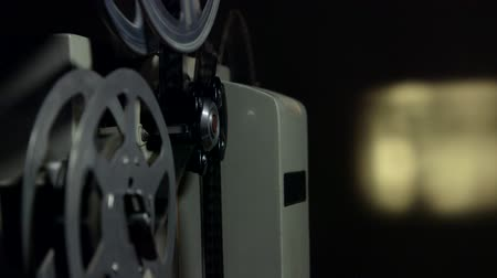 Screening movies on vintage 16 mm film projector tracking shot