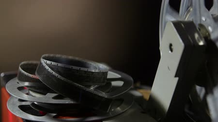 tiras : Film reel on movie projector with flickering screen in the background