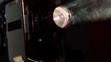 projetor : Vintage 16 mm movie projector projecting film in a dark room tracking shot