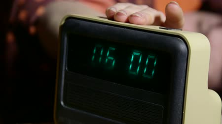clock hands : Woman waking up and stopping alarm clock lying in bed at home