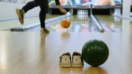 штифт : Bowling alley with shoes and ball, in the background woman playing Стоковые видеозаписи