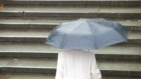 andar : Woman with umbrella goes up the stairs under heavy rain