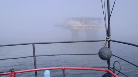 rigs : Vessel moving to offshore gas platform in the misty sea
