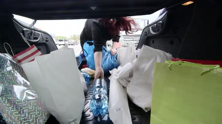 zsák : Woman unloads groceries in plastic and paper bags into the trunk of her car after shopping in supermarket Stock mozgókép