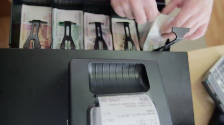 регистр : Cash register prints a receipt for the customer, cashier giving change in russian banknotes