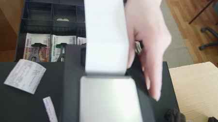 roll : Cashier loading cash register paper roll