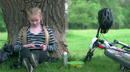 hareketli : Teenage girl with bicycle sitting under tree, using tablet pc Stok Video