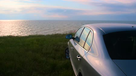 superb : Car parked on the seashore at sunset, rear view