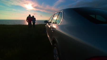 superb : Adult couple silhouette near his car enjoying view of the sea coast at sunset