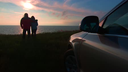 superb : Adult couple silhouette near his car on sea coast watching the sunset