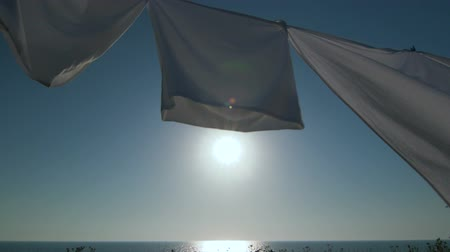 prendedor de roupa : Laundry drying on clothesline against blue sky and sun