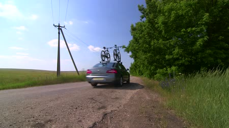 sport skoda : Car with two bicycles on bike roof carrier driving down a country road