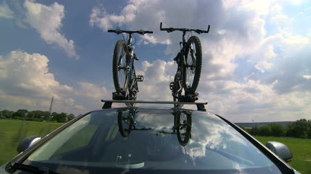 sport skoda : Car driving with two bicycles mounted on bike roof carrier POV