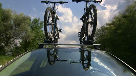 sport skoda : Car with two bicycles on bike roof carrier driving along a country road POV Stock Footage