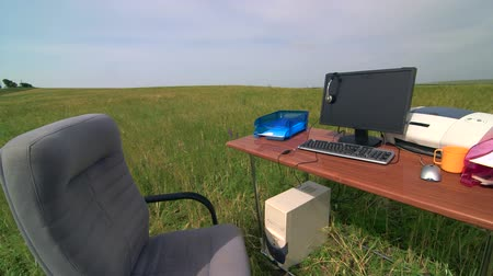 helyek : Place of work for telecommuter - personal computer and supplies on a desk in green field Stock mozgókép