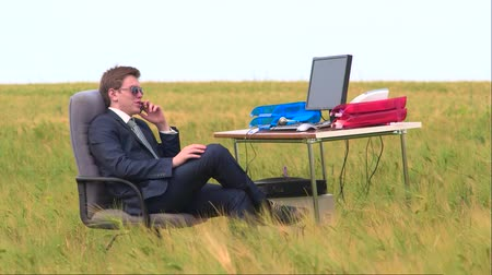 masaüstü : Young business man speaks by phone sitting at a desk with computer in wheat field