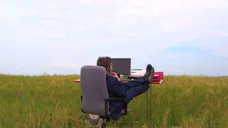 usuário : Business man wearing headset during telephone conversation at office desk in a green field