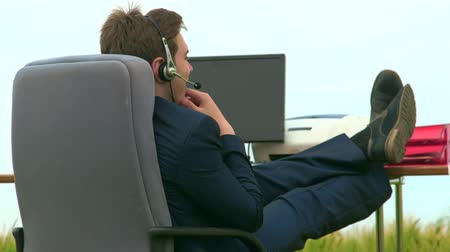 pomocník : Business person wearing headset during VoIP conversation at office desk outdoors