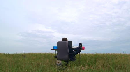 comfortable : Business man relaxing at office desk in a green field