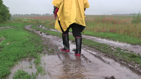 bota : Man wearing yellow raincoat goes on a dirt country road through the field in rain