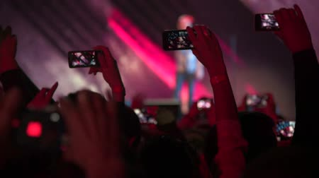 фотографий : People taking photos or recording video with their smart phones at music concert  Стоковые видеозаписи