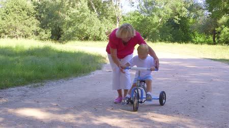 бабушка : Grandmother assisting child to ride a bicycle in summer park