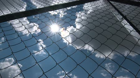 entrance : Sun shining through the chain link iron wire fencing