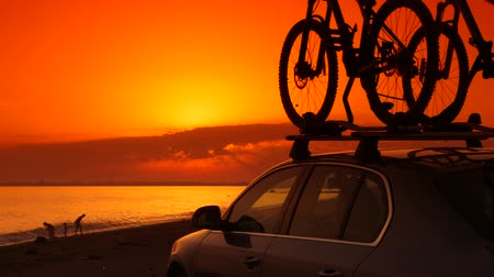 vacation destination : Active family summer beach vacations, silhouette of car with mounted bicycles family in background  Stock Footage
