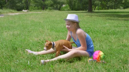 animais e animais de estimação : Happy child playing with her puppy dog at grass in summer park