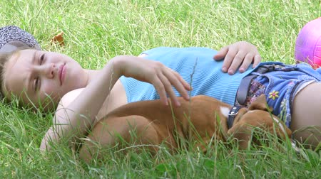 small park : Tired child with puppy relaxing on the grass in summer garden