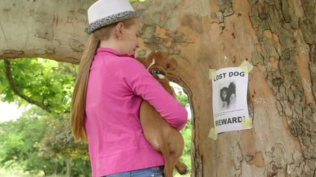 kaybetmek : Child with puppy reads the lost pet sign on tree trunk