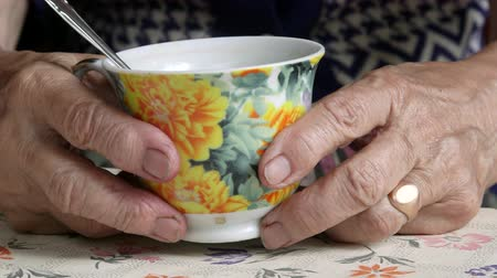 necessity : Senior woman hands holding cup of some drink