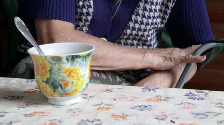necessity : Elderly woman hands at the table with a cup of some drink close-up Stock Footage