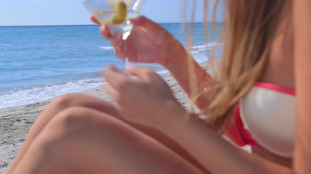 kumlu : Young woman drinking martini cocktail on the summer sandy beach, focus on background
