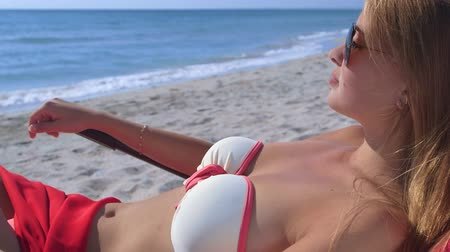 banhos de sol :  Young woman sunbathing in lounge chair on summer sandy beach  Vídeos
