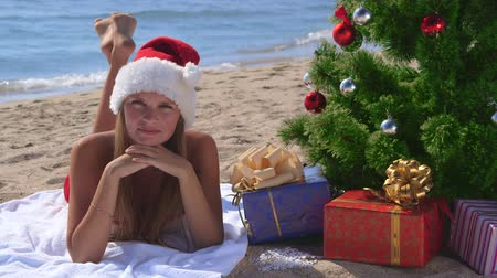 ležící : Girl in Santa hat celebrating Christmas on tropical beach looking at the camera smiling