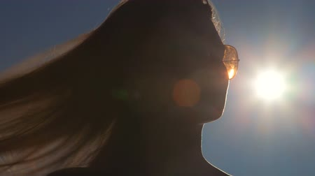 Young woman face in sunglasses against the sun lens flare Stock Footage