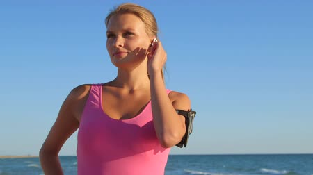 vezeték nélküli : Fitness athletic girl using sport wireless headset while exercising on the beach medium shot