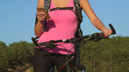 cyclists : Active young woman cyclist on bicycle using smart phone during cycling workout outdoors close-up