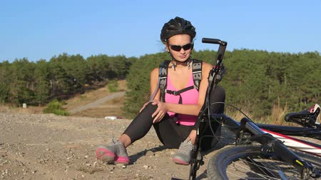 diz : Workout fitness injuries young woman cyclist sitting near his bike with pain in knee joint after cycling outdoors