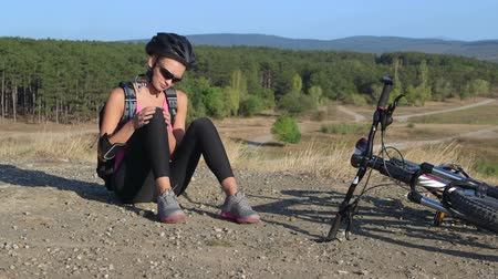 kolano : Workout fitness injuries young woman cyclist sitting near his bike with pain in knee joint after cycling outdoors