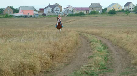 toprak : Young girl riding horse across the field from village