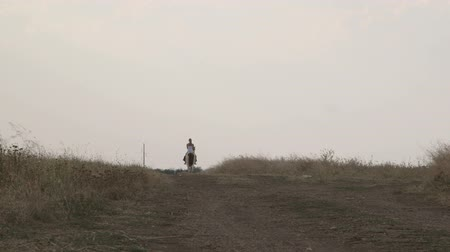 rotaları : Young girl riding horse down the trail in countryside long shot